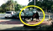 Người đàn ông dùng tay không nâng xe hơi