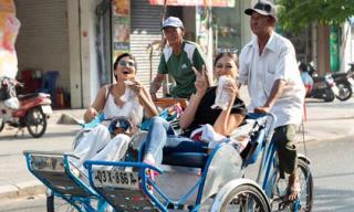 H'hen Niê cùng Hoa hậu Hoàn vũ Nhật dạo Sài Gòn bằng xích lô, đội nón lá, vô tư 'gặm' bánh mì
