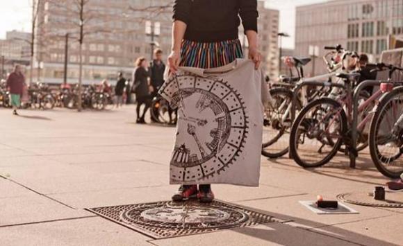 người phụ nữ đặt quần áo trên nắp cống, thời trang, sản phẩm thời trang từ nắp cống
